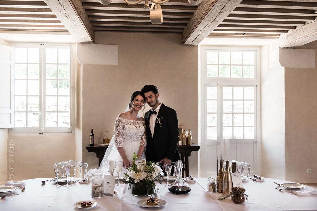 mariés à la table d'honneur mariage or et blanc